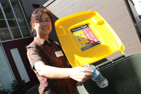 Lady with plastic bottle going in bin_website.jpg